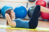Young woman doing abs in the gym.