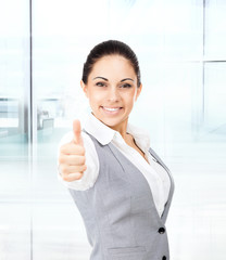 Business woman thumb up gesture, in modern office