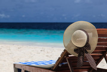 straw hat on a lounge chair at tropical beach