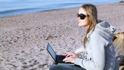 Woman in sunglasses using laptop on the beach