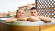 Portrait of a smiling young couple enjoying Jacuzzi.