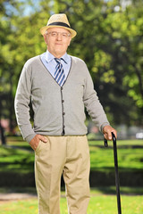 Carefree senior gentleman with a cane posing in park