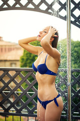 Young beautiful woman taking a shower outdoors wearing a bikini