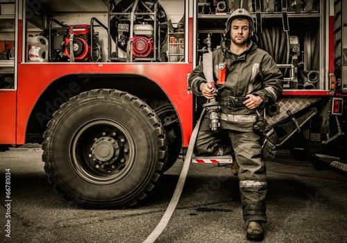 Firefighter near truck with equipment - 66781034