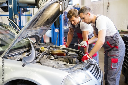 Deurstickers Two mechanics fixing car in a workshop