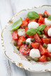 Caprese salad with capers on a plate, vertical shot, close-up