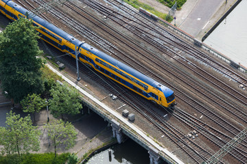 Aerial view of Dutch train at a bridge crossing a canal