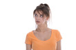 Isolated disappointed girl in orange shirt looking doubtful and