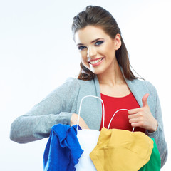 Woman show thumb up, hold clothes, shopping bag.
