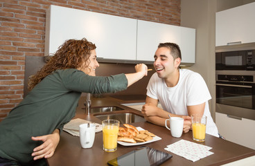 Happy girl feeding her boyfriend in a breakfast
