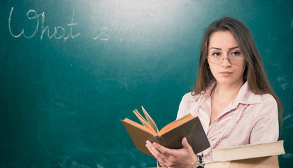young female teacher at blackboard with open book