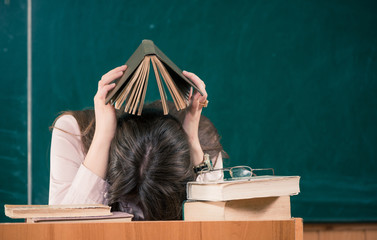 tired teacher with open book above head