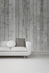 Greyscale image of a sofa against a concrete wall