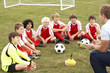 canvas print picture - Junior football team training with coach