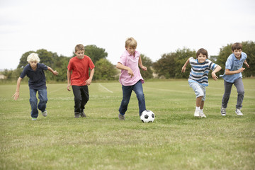 Boys playing with football in park