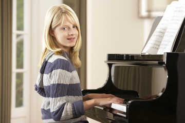 Girl playing grand piano at home