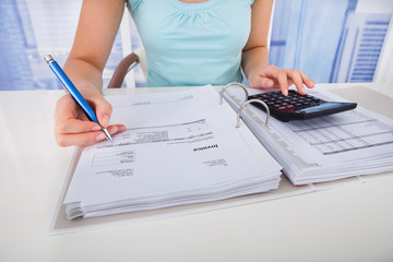 Woman Calculating Home Finances At Desk