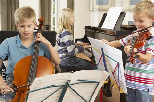 Leinwanddruck Bild Children playing musical instruments at home