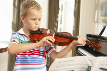 Young boy playing violin at home
