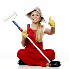 Woman with paint roller shows thumb up