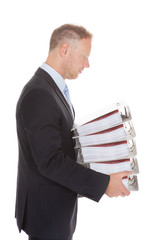 Sad Businessman Carrying Stack Of Binders