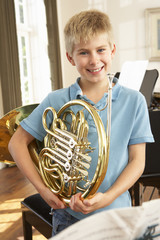 Boy holding French horn at home