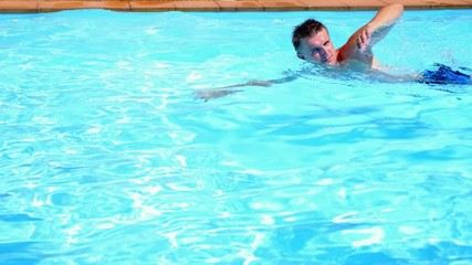 Young Tanned Man Swimming the Crawl in a Pool. Sunny Summer Day.