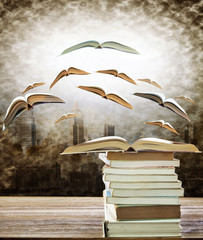 abstract of open book on stack and flying book to the light over