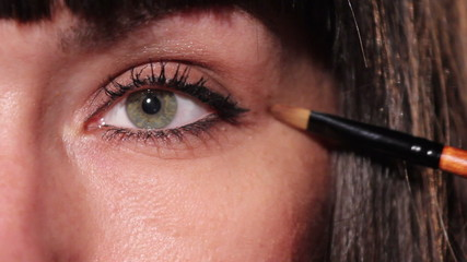 Young beautiful brunette make up eyes and lashes with a brush