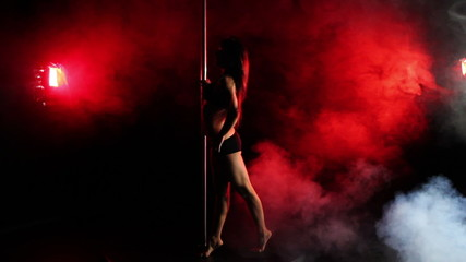 Beautiful young slender girl is plastic pole dancing in the dark