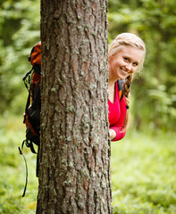 Young woman hiker behind a tree