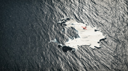 Aerial of red airplane flying over melting iceberg in ocean.