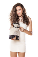 girl holding a magnifying glass and looking in her handbag