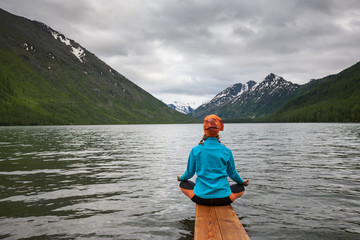 Woman is doing yoga at Multinskoe lake in Altai mountains, russi