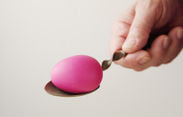 Man holds spoon with Easter egg