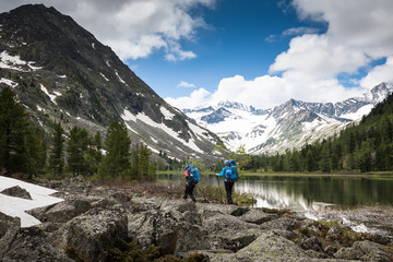 Hikers are walking by mountain lake in Altai mountains, Russia