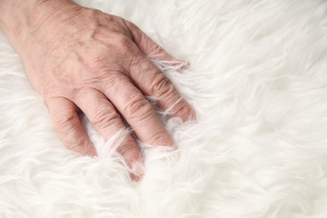 Hand of a man on faux sheepskin