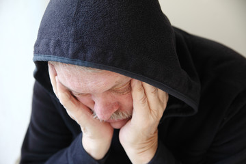 Sad older man in hooded jacket