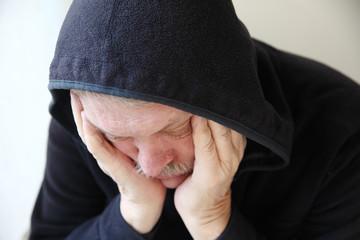 Sad older man in hooded jacket