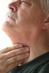 Man with hand on throat