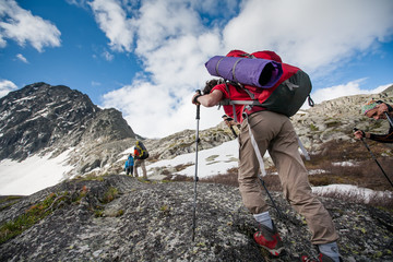 Hikers are climbing rocky slope of mountain in Altai mountains,