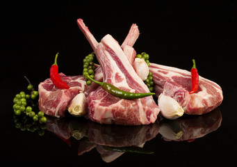 Raw lamb chops with spices and herbs