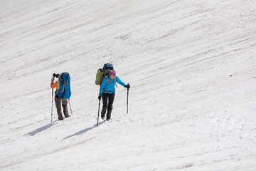 Backpacker passes snow field in rocky mountain in Altai mountain