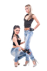 Two young sexy women in denim jeans isolated on white
