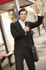 Businessman hailing bus at stop
