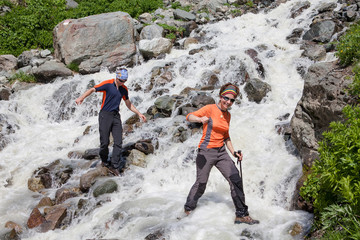 Trekkers are crossing mountanious river in Zemo (upper) Svaneti,
