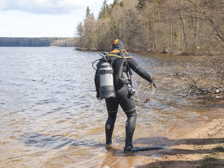 diver emerges from the lake in the summer