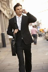 Businessman on phone walking down street