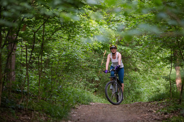 Woman is cycling in spring forest