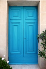Closed turquoise wooden front door